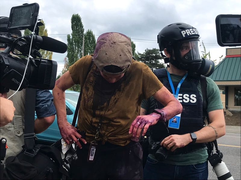 PMG PHOTO: ZANE SPARLING - Local journalist Maranie Staab is led away from the street clash after being doused in paint and chemical spray.