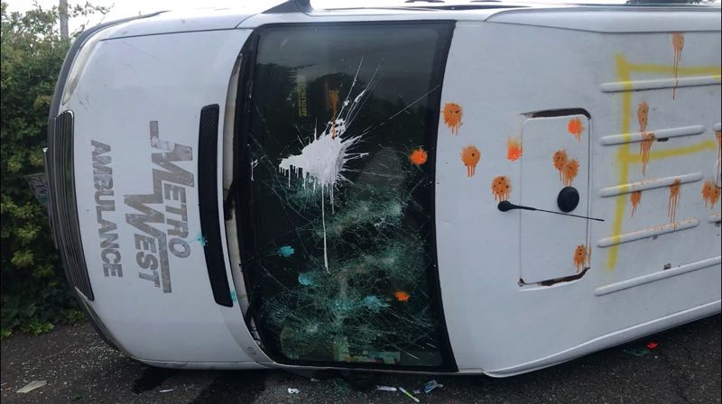 PMG PHOTO: ZANE SPARLING - A van with the markings of Metro Ambulance West on its hood was overturned by Proud Boys on Sunday, Aug. 22 in the parking lot of an abandoned Kmart store.