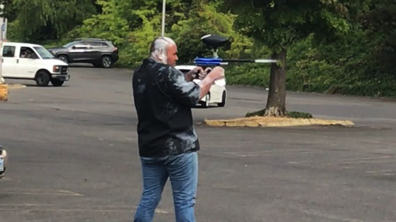 PMG PHOTO: ZANE SPARLING - Tusitala Toese, better known by his nickname Tiny, fires an air rifle at antifa during a violent clash on Sunday, Aug. 22 in Portland.
