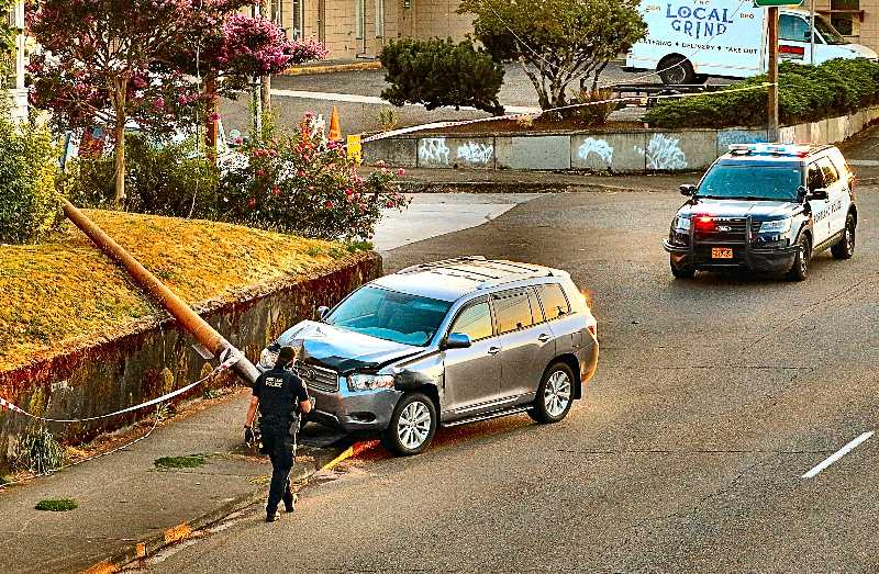 DAVID F. ASHTON - A PPB officer examines the steel utility pole, and the smashed Toyota SUV that toppled it., on S.E. Powell Boulevard, eastbound at 8th Avenue.