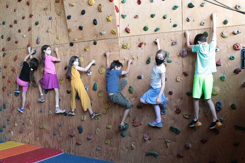 DAVID F. ASHTON - Some of the campers headed down from Tucker Maxon Schools unique treehouse, ready for their next activity - climbing the wall in the gym!