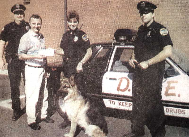 CENTRAL OREGONIAN - August 29, 1996: Prineville Police officers receive a $2,000 check from Allstate representative Fred Gerke. From the left, Capt. Tim Pinkston, Fred Gerke, handing the check to officer Andrea Donham, Valko, and D.A.R.E. officer Frank Hueregue.