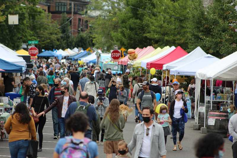 PMG PHOTO: COURTNEY VAUGHN - Multnomah Days attendees line Capitol Highway mid-day during the neighborhood street fair. Event organizers encouraged attendees to wear masks in crowded spaces throughout the festival.