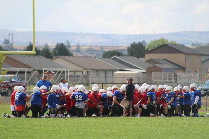 ANDY DIECKHOFF/MADRAS PIONEER - MHS football head coach Kurt Taylor addresses his varsity and JV teams during a scrimmage.