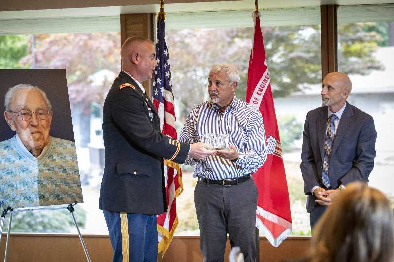 PMG PHOTO: JAIME VALDEZ - Col. Michael Helton, left, commander for the Corps Portland District, presents Don Ossey the 2021 U.S. Army Corps of Engineers Distinguished Civilian Award for the Portland District posthumously in honor of his father Bud Ossey as Steve Miles looks on. A ceremony honoring Ossey was held Aug. 17 at Tualatin Country Club.