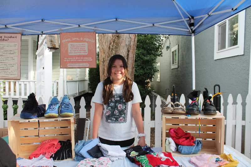 PMG PHOTO: HOLLY BARTHOLOMEW - PJ Wagner sold used clothing at her stand at the West Linn Summer Market. Proceeds went to the Child Labor Coalition.