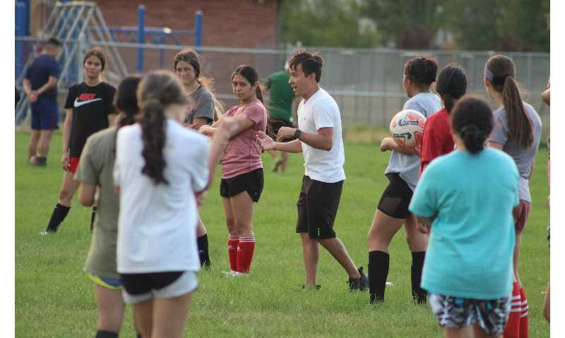 ANDY DIECKHOFF/MADRAS PIONEER - Head coach Shawn Darrow, center, instructs the Madras High School girls' soccer team during an August practice.