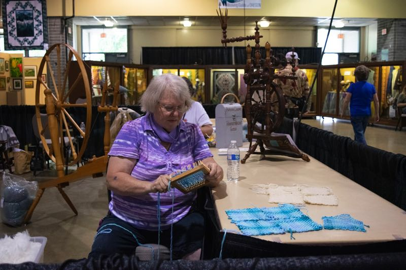 PMG PHOTO: SALLY SEGAR - Judith Bartel from Salem weaves on a pin loom, making squares that she'll turn into mug rugs. She might make the wool ones (the white ones) into a hot plate.