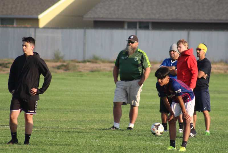 ANDY DIECKHOFF/MADRAS PIONEER - Seniors Israel Estrada, left, and Luis Benitez, right front, will try to lead the Madras boys' soccer team to a Tri-Valley Conference title. Head coach Clark Jones, center, noted that the TVC is one toughest leagues in 4A soccer.