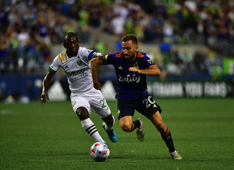 COURTESY PHOTO: JANE GERSOVICH/SOUNDERS FC COMMUNICATIONS - Portland's Diego Chara and Seattle's Nicolas Benezet battle in midfield on Aug. 29 during a match the Timbers won 2-0 at Lumen Field in Seattle.