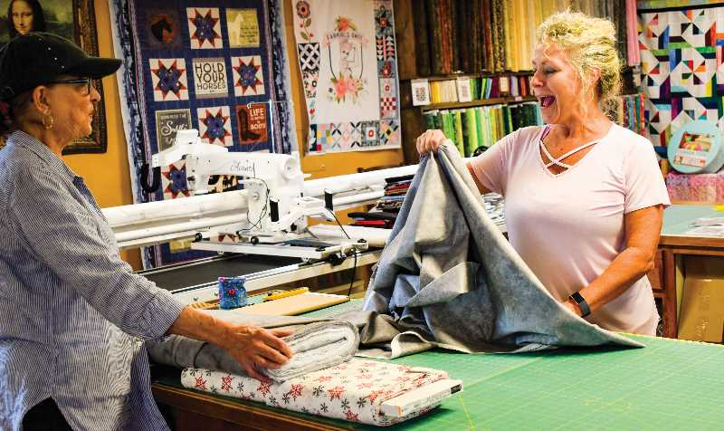 RAMONA MCCALLISTER - Rhonda Krider measures out fabric for a customer. Between them is Krider's long arm quilting machine that she rents out. The walls display colorful quilts that she has made, and quilting material is visible in the background.