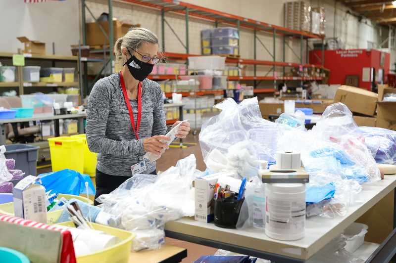 PMG PHOTO: JONATHAN VILLAGOMEZ - Gloria Schwindt helps sort and package a variety of medical supplies headed for Haiti, part of Medical Teams Internationals efforts to help the country hurting from a recent earthquake.