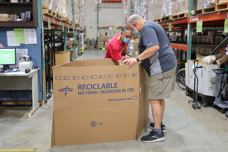PMG PHOTO: JONATHAN VILLAGOMEZ - Volunteers sort through boxes in Medical Teams Internationals large warehouse last week, searching for walkers and crutches to send to Haiti.
