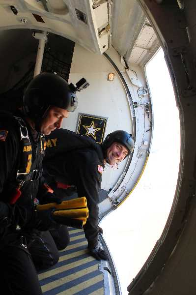 PHOTO BY SHANNAN AHERN  - Devin Diaz, left, and Jesse Robins, members of the U.S. Army Golden Knights Parachute Team, prepare to drop streamers Saturday to determine wind elements prior to their parachute performance at the Airshow of the Cascades. The Golden Knights were the feature act.