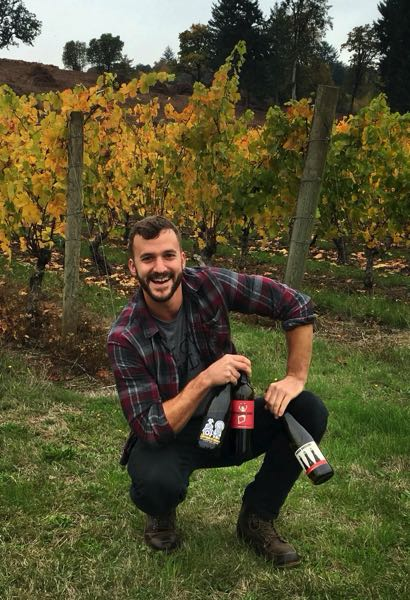 COURTESY PHOTO: NATE BENTLEY - Nate Bentley poses with an assortment of his Old Salt Cellar wines in front of the now-defunct Witness Tree Vineyard, where he got his start as a winemaker in 2014.