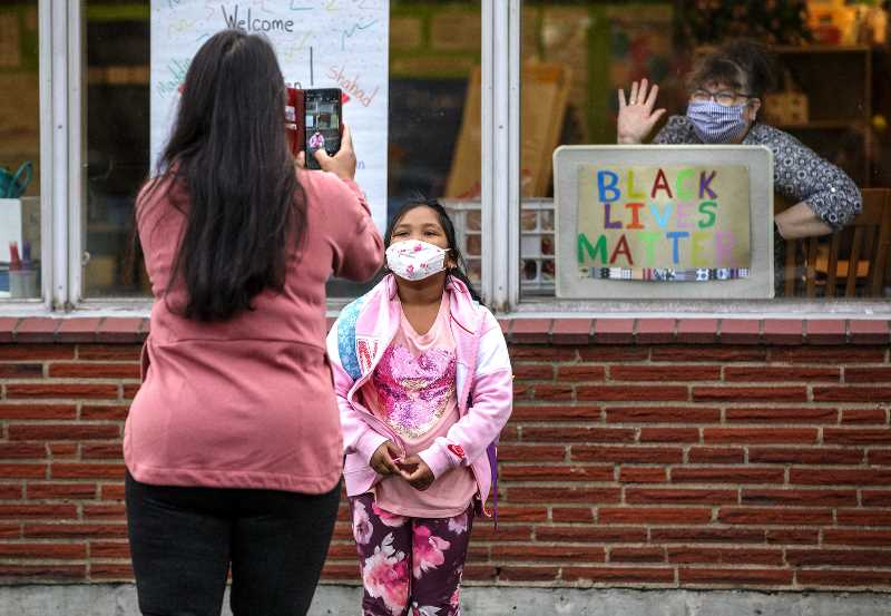 PMG PHOTO: JONATHAN HOUSE - Jason Lee Elementary School kinder educational assistant Stephanie Corbett waves as Racheeta Rajbhandari has her photo taken on the first day of in-person, hybrid learning in spring 2021. Portland students will go back to school, starting Sept. 1.