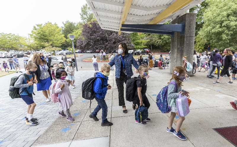 PMG PHOTO: JONATHAN HOUSE - Oak Creek Elementary School teacher Laura Johnson guides her students into the building on the first day of school.