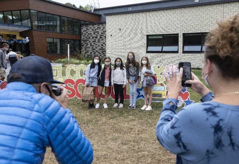 PMG PHOTO: JONATHAN HOUSE - Oak Creek Elementary School students take pictures in front of the building on the first day of class.