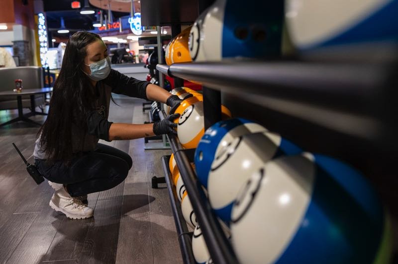 PMG PHOTO: JAIME VALDEZ - Aaliyah Valenzuela, an employee at Bullwinkle's, faces bowling balls during her shift. Valenzuela will be going back to school in the middle of September.
