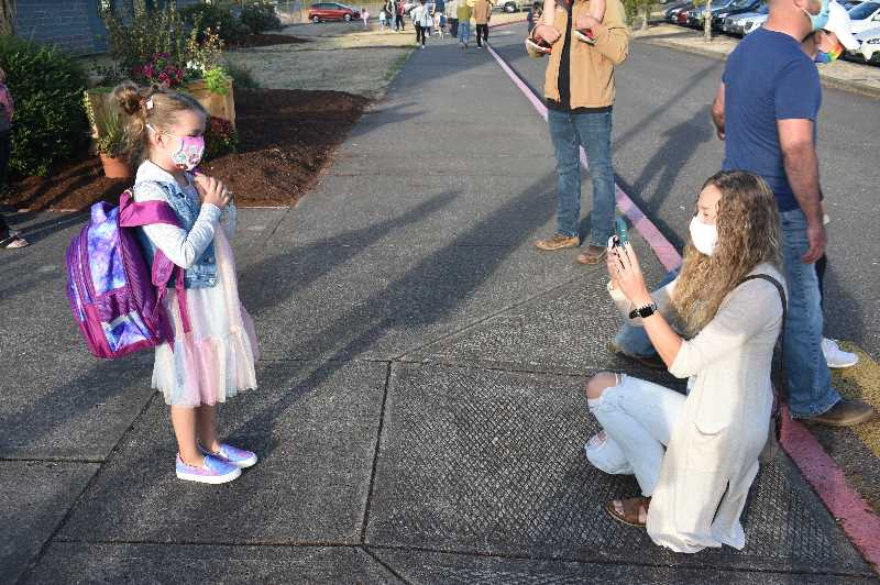 PMG PHOTO: ANGEL ROSAS  - Chelsey Hargens takes a quick photo of her daughter Ella Hargens before she is taken to her first grade class.