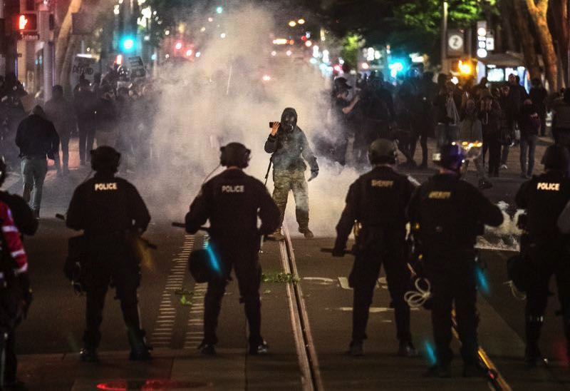 PMG FILE PHOTO - Portland Police Bureau officers face off with a protest crowd downtown.