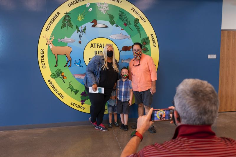 PMG PHOTO: JAIME VALDEZ - North Plains City Councilor Trista Papen, her husband, Alex Ugarte, and their two children, Emerson, 3, and Ethan, 5, in front of a seasonal round in the cafeteria of Atfalati Ridge Elementary School. Ethan will start at the new school as a kindergartener.