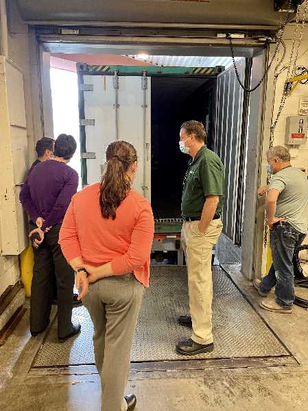 COURTESY PHOTO: PROVIDENCE HEALTH - Providence Portland staff inspect a refrigerated truck at a loading dock. Providence is temporarily bringing in large refrigerated trucks to use as overflow morges due to a surge of COVID-19 patients.