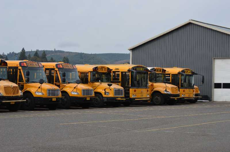 PMG FILE PHOTO - A row of buses sits outside a garage in Scappoose in 2015.