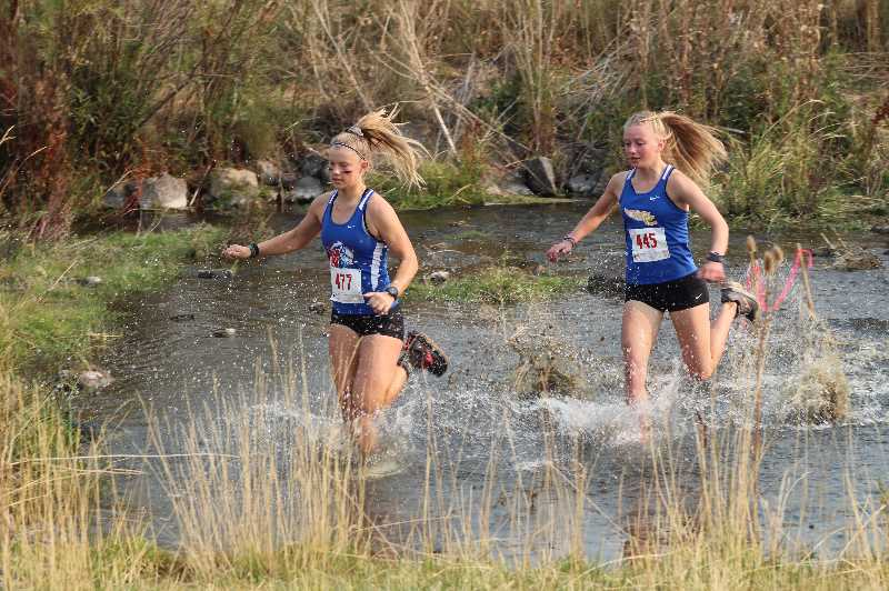 ANDY DIECKHOFF - Madras runner Hannah MacDuffee, left, and Crook County's Lindsey Mode splash through the water element of the Jere Breese Memorial Stampede Saturday, the cross-country season kickoff event at the Breese Ranch east of Prineville. Mode took third to lead Crook County.