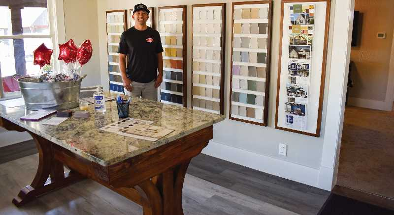 RAMONA MCCALLISTER - Blaine Noland stands by his Sherwin Williams paint display, complete with a granite table, donated by Oceanic and Design out of Redmond. The flooring was donated as a showpiece by Third Street Flooring.