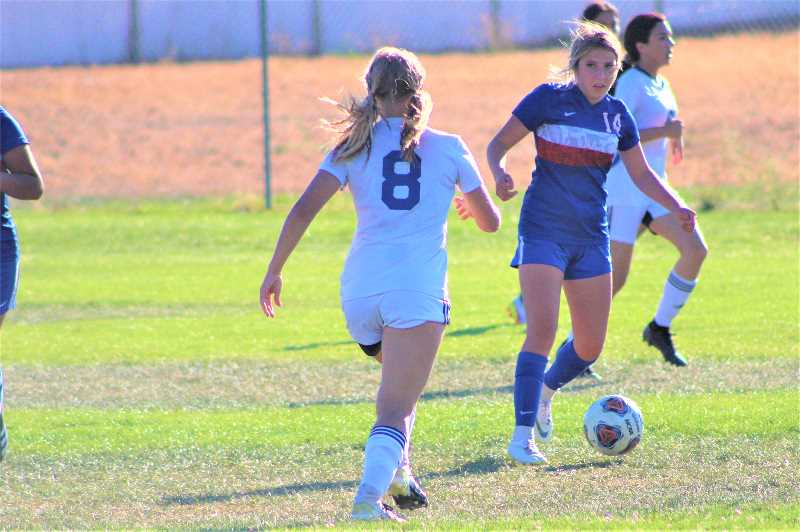 ANDY DIECKHOFF/MADRAS PIONEER - Madras junior Natalie Lockey (14) prepares to dribble around a Crook County defender before delivering the assist on the game-winning goal.