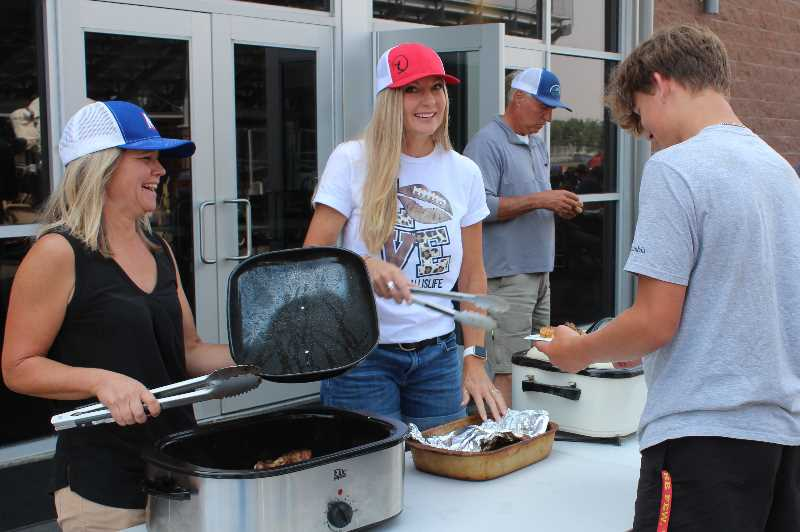 ANDY DIECKHOFF/MADRAS PIONEER - Team moms Kim Stout, left, and Heidi Boyle serve barbecue chicken, as is tradition before MHS home games.