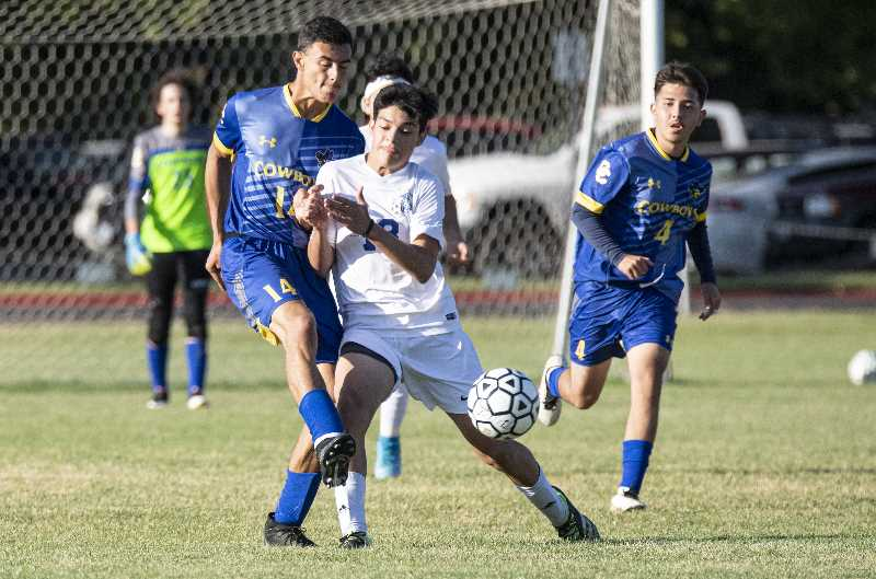 LON AUSTIN/CENTRAL OREGONIAN - Madras freshman Hansel 'Steve' Gonzalez, in white, jostles with a Crook County opponent during a 3-2 win.