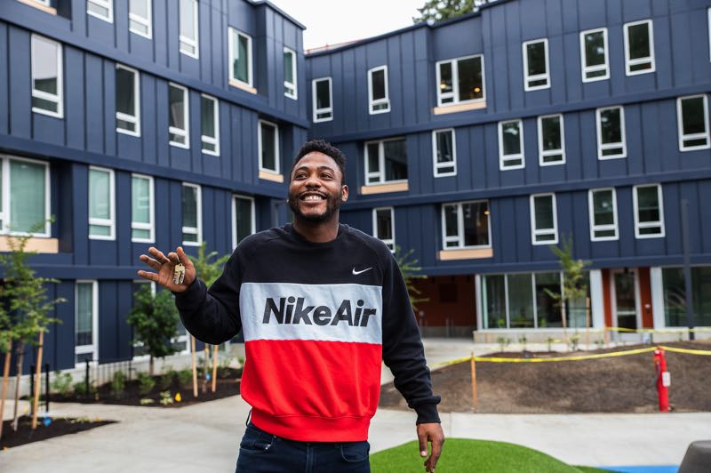 COURTESY PHOTO: HACIENDA CDC - A resident gets his key to a unit at Rockwood Village — a new affordable housing development in East Multnomah County.