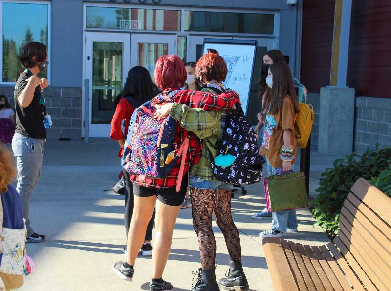 MIA RYDER-MARKS - Two students embrace one another on the first day of school.