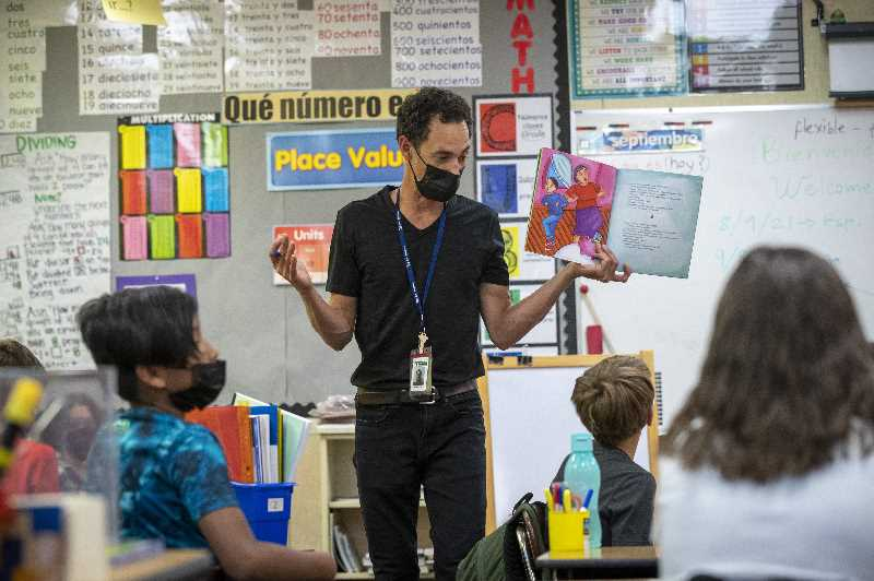 PMG PHOTO: JAIME VALDEZ - Jorge Porrata, a fourth grade two-way immersion teacher at Bridgeport Elementary School, reads a book to his class on the first day of school Wednesday.