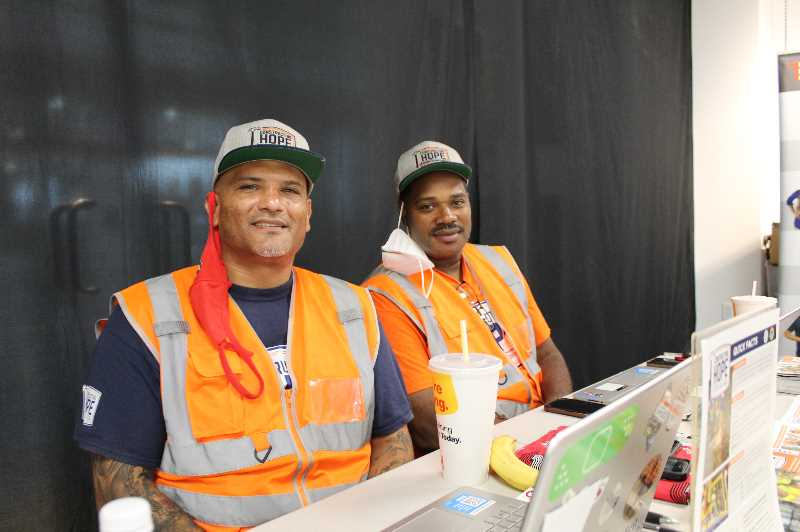 """PMG PHOTO: JOSEPH GALLIVAN - Marcus Ball (left) was there on behalf of Constructing Hope, a """"second chance"""" organization that helps people overcome barriers and enter the construction industry. (They agreed to lower their masks briefly for the photograph.)"""
