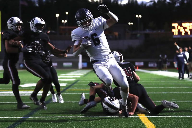 PMG PHOTO: JAIME VALDEZ - Lake Oswego running back Calvin Macy (6) escapes from Sherwood's Treyvin Fischer (36) and Luke Wert (24) for a touchdown on Friday, Sept. 10 at Sherwood High School.