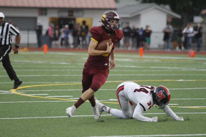 PMG PHOTO: WADE EVANSON - Forest Grove quarterback Kaden Hale scrambles from the pocket during the Vikings' 24-21 win over McMinnville Friday night, Sept. 10, at Forest Grove High School.