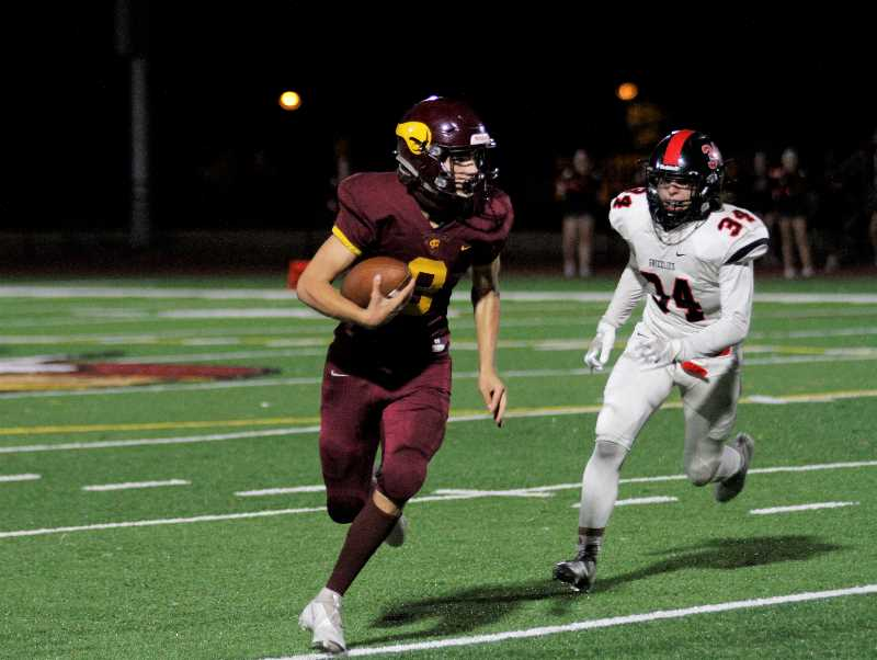 PMG PHOTO: WADE EVANSON - Forest Grove quarterback Kaden Hale scrambles from the pocketduring the Vikings' 24-21 win over McMinnville Friday night, Sept. 10, at Forest Grove High School.