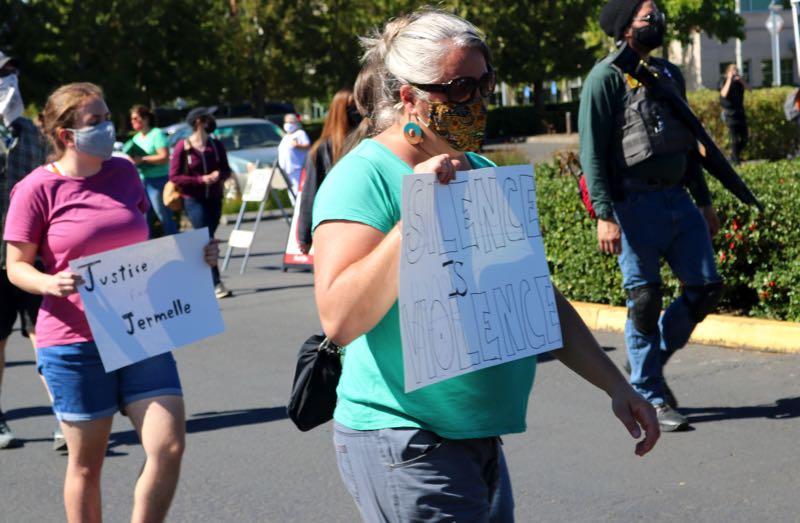 PMG PHOTO: ZANE SPARLING - A woman carries a sign reading, 'Silence is Violence,' as protesters marched through the Clackamas County Red Soils Campus during a protest in honor of Jermelle Madison on Saturday, Sept. 11.