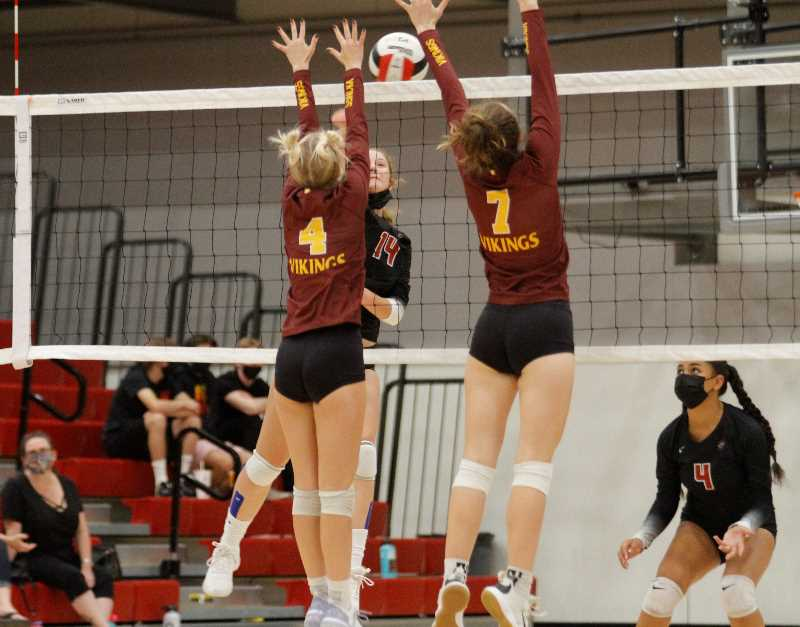 PMG PHOTO: WADE EVANSON - Sherwood's Liv Van Austen rises for an attack versus Forest Grove defenders during their match Sept. 9 at Sherwood High School.