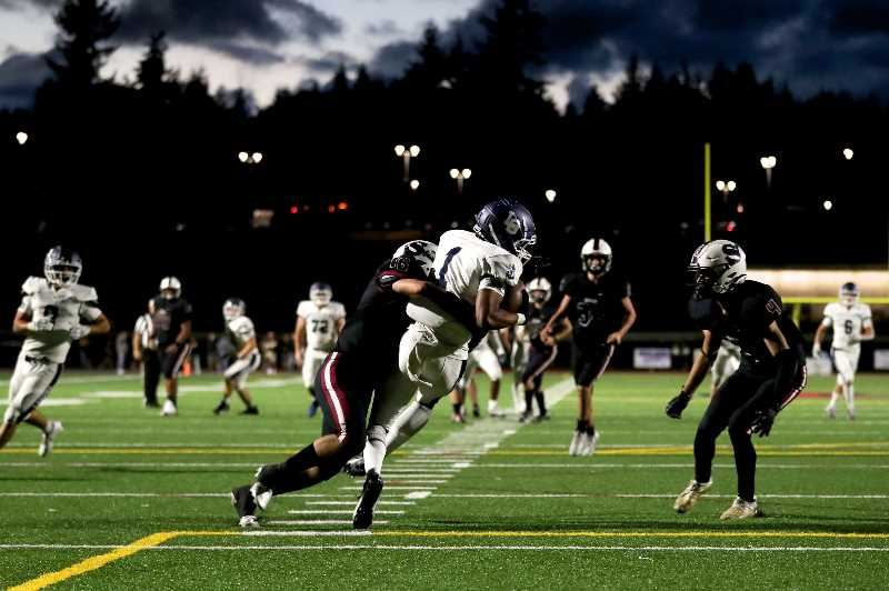 JAIME VALDEZ-PORTLAND TRIBUNE - Lake Oswego Lakers wide receiver Justus Lowe (1) hauls in a reception over Sherwood defenders Friday night, Sept. 10, at Sherwood High School. The Lakers defeated the Bowmen 48-20.