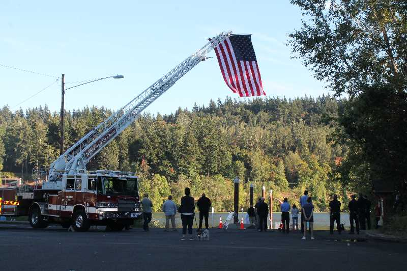 PMG PHOTO: HOLLY BARTHOLOMEW - A large flag hangs over the Honoring Those Who Serve Ceremony at Willamette Park in West Linn.