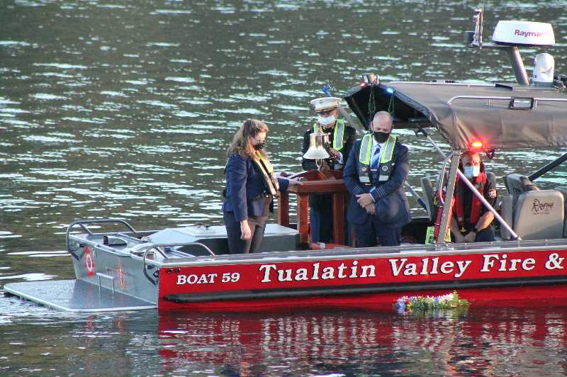 PMG PHOTO: HOLLY BARTHOLOMEW - West Linn Mayor Jules Walters and Captain Wayne Ayers watch a flower wreath float down river after laying it on the water.