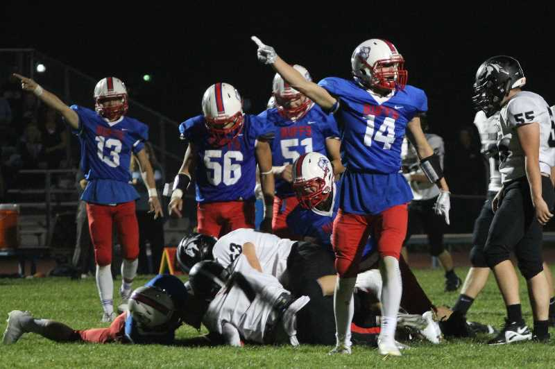 ANDY DIECKHOFF/MADRAS PIONEER - Madras pass rusher Reece White (14) and safety Ethan Graeme (13) signal a turnover in the first quarter.