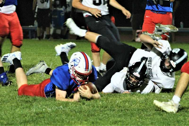 ANDY DIECKHOFF/MADRAS PIONEER - Madras quarterback Dru Boyle falls forward for positive yardage. Boyle had the Buffs' only offensive touchdown of the night, a four-yard rushing score in the fourth quarter that sealed the victory for MHS.