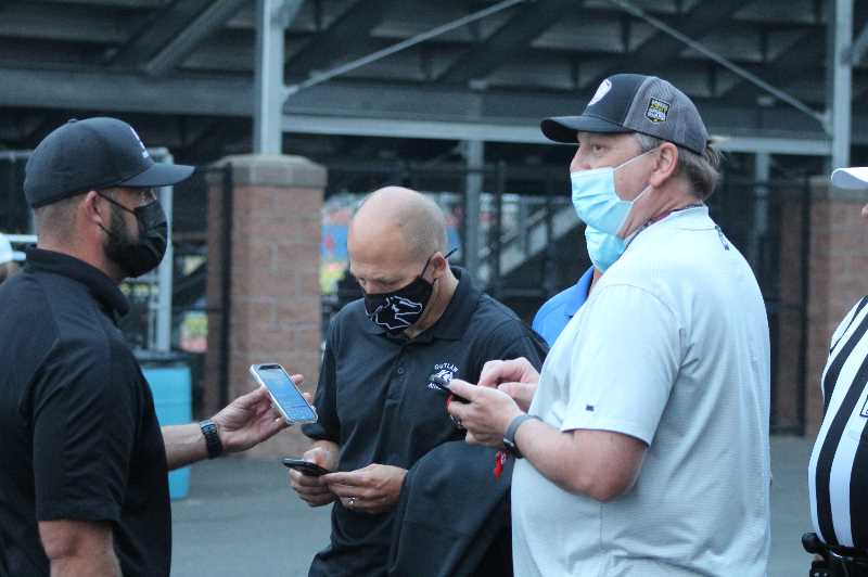 ANDY DIECKHOFF/MADRAS PIONEER - Madras High School athletic director Daniel Barendse, right, spent Thursday evening refreshing his phone for AQI updates alongside the head football coach and athletic director from Sisters High School.