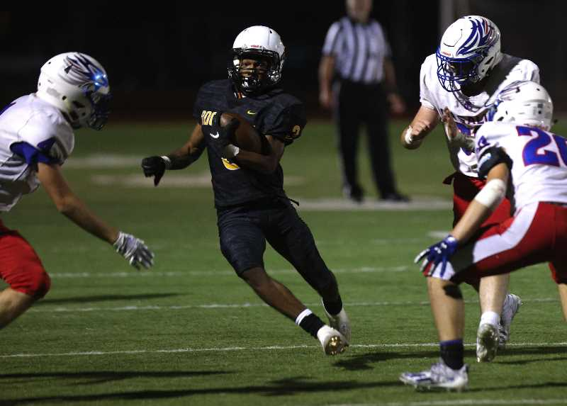 PHOTO BY JONATHAN HOUSE - Roosevelt football's Lindell Betts, center, makes a cut against La Salle Prep on Friday, Sept. 10, 2021, at Roosevelt High School.