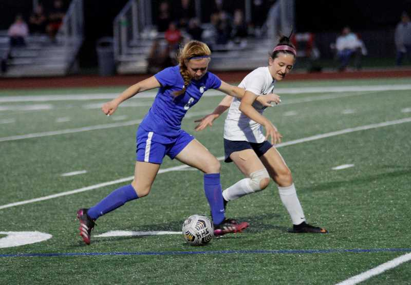 PMG PHOTO: WADE EVANSON - Hillsboro's sophomore defender Natalia Freimuth fights off a Hood River Valley player during the Spartans 4-0 win over the Eagles Tuesday night, Sept. 14, at Hillsboro High School.